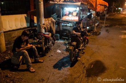 menambal ban motor beberapa menit sebelum tengah malam